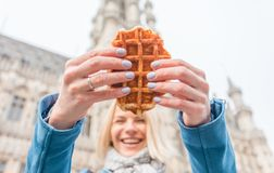 Young beautiful woman holding a traditional Belgian waffle on the background of the Great Market Square in Brussels stock photography