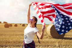 Young beautiful woman holding USA flag Royalty Free Stock Image