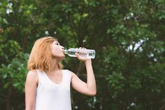 Young beautiful woman holding water at green park. Young beautiful woman holding water at green park background stock images