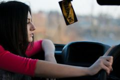 Young beautiful woman holding the wheel. Hangs a badge of warning. Woman driver stock photos