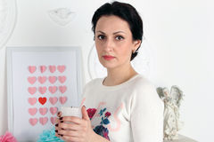 A young beautiful woman holding a white candle. In the background is a picture with hearts and angel statuette. Her hair is pulled back in hairstyle Royalty Free Stock Image