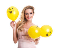 Young beautiful woman holding yellow smiley balloons, valentine' Stock Images