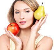 Young beautiful woman holds the apple and pear. Royalty Free Stock Images