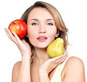 Young beautiful woman holds the apple and pear. Royalty Free Stock Photos