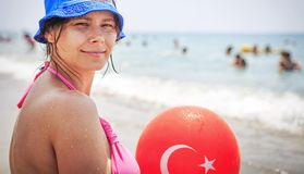 Young beautiful woman holds balloon with turkish flag on it on tropical beach on summer sunny day. Resort in Turkey. royalty free stock photo