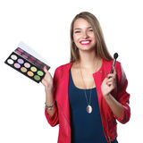 Young beautiful woman holds in one hand and a palette with paint and shadows for makeup, second hand brush for makeup Stock Images
