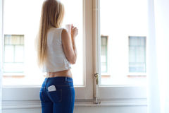 Young beautiful woman at home with mobile phone in back pocket. Royalty Free Stock Images