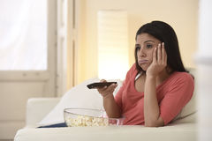 Young beautiful woman at home watching television tired and bored Stock Images