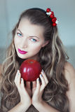 Young beautiful woman with hoop in hair and apple in hands Royalty Free Stock Image