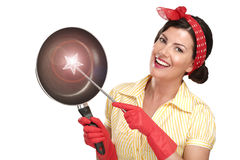Young beautiful woman housewife showing a magic wand on dishes Stock Photo