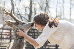 Young beautiful woman hugging animal ROE deer in the sunshine royalty free stock photos