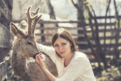 Young beautiful woman hugging animal ROE deer in the sunshine stock photography