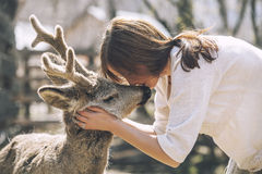 Young beautiful woman hugging animal ROE deer in the sunshine royalty free stock image