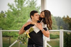 Young and beautiful woman hugging her boyfriend from back. Young and beautiful women with bouquet of flowers hugging her boyfriend from back on the green Stock Images