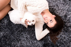 Young beautiful woman hugging her puppy. A young, beautiful woman in underwear lying on the carpet and hugging her cute little puppy Stock Image