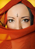 Young beautiful woman indian traditional eyes. Young beautiful woman eyes in indian traditional jewellary, bindi , sari dress and makeup. yellow background Stock Photography