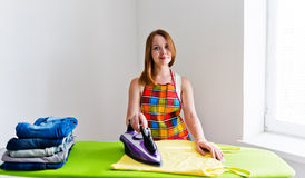 Young beautiful woman ironing clothes Stock Photography