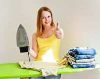 Young beautiful woman ironing clothes in room Royalty Free Stock Photography