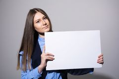 Young beautiful woman in a jacket with blank sheet Royalty Free Stock Photo