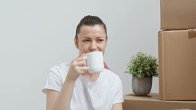 Young beautiful woman in jeans and a white T-shirt is drinking coffee while sitting on the floor against a background of. Cardboard boxes. The concept of stock footage