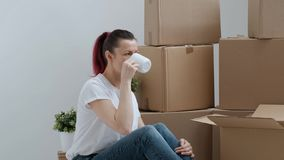 Young beautiful woman in jeans and a white T-shirt is drinking coffee while sitting on the floor against a background of. Cardboard boxes. The concept of stock video footage