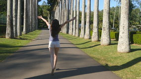 Young beautiful woman jogging and spinning along exotic parkland and having fun. Happy girl is running in tropical park Stock Images