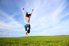 Young beautiful woman jumping for joy. On green sunny field stock photos