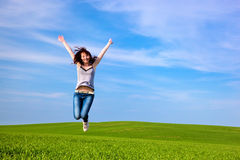 Young beautiful woman jumping for joy. On green sunny field royalty free stock photo