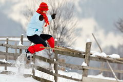 Young beautiful woman jumping over fence Royalty Free Stock Photography
