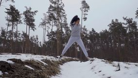 Young beautiful woman jumping over ravine and training her legs. Young beautiful woman wearing sportswear and snickers is training her legs and endurance. Pretty stock video