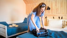Young beautiful woman jumping on suitcase trying to close it stock photos