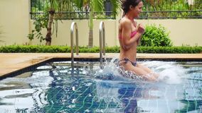 Young beautiful woman jumping into swimming pool in slow motion. 1920x1080 stock video footage