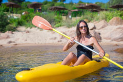 Young beautiful woman kayaking in clear turquoise Royalty Free Stock Images