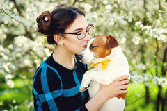 Young beautiful woman kisses her beloved pet dog Jack Russell terrier on a background of spring blooming trees royalty free stock photos