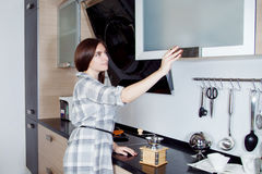 Young beautiful woman in kitchen, takes off shelf tools for cooking Royalty Free Stock Images