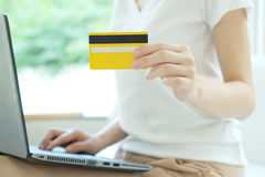Young beautiful woman with laptop and credit card at home Stock Photography