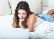 Young beautiful woman with laptop notebook on bed in bedroom home surfing internet Royalty Free Stock Photography