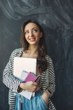 Young beautiful woman with laptop and notes in hands smiling stock photography
