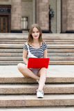 Young beautiful woman with laptop sitting on stairs near the university Stock Images