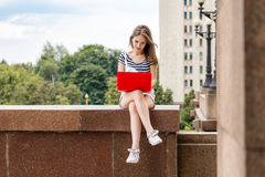 Young beautiful woman with laptop sitting on stairs near the university Stock Photography