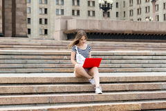 Young beautiful woman with laptop sitting on stairs near the university Stock Photo