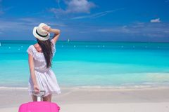 Young beautiful woman with large suitcase on tropical beach Royalty Free Stock Photos