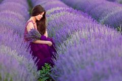 Young beautiful woman in lavender fields with a romantic mood. In the summer time wearing a purple dress