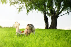 Young beautiful woman lays on green field Royalty Free Stock Images