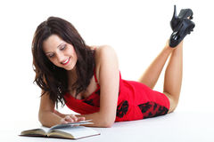 Young beautiful woman lays and reads book isolated Royalty Free Stock Photos