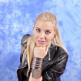 Young beautiful woman in a leather jacket on her arm wide bracelets. Young beautiful woman in a leather jacket on her arm wide bracelets royalty free stock photo