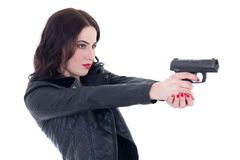 Young beautiful woman in leather jacket shooting with gun isolat Stock Photo