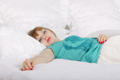 Young beautiful woman lies on bed with white linen Royalty Free Stock Photography