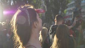 Young beautiful woman lifting hands and cheering up on street during festival, happy, crowd of fans standing around stock video footage