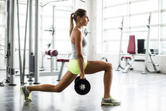 Young beautiful woman lifting weights in a gym. Focused young beautiful woman lifting weights in a gym Royalty Free Stock Photos